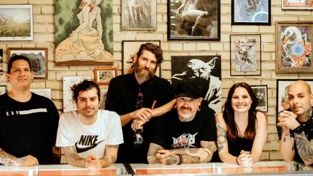 The San Marcos Tattoo Emporium team poses in front of a wall covered with art.